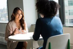 感情をコントロールする方法としては誰か(できればコーチやカウンセラーのような第三者)に話すことも非常に有効です。話し合う女性の画像。